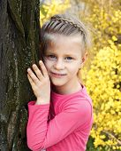 Little Girl Stands Leaning Against A Tree