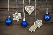 stock photo of ginger bread  - Christmas Background Decorated Ginger Breads and Blue Christmas Balls Hanging on Wood - JPG