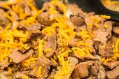 foto of shredded cheese  - Sliced beef cooked with onions with shredded cheese - JPG