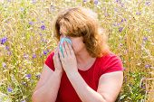 stock photo of rhinitis  - Fat woman with allergic rhinitis in the meadow - JPG