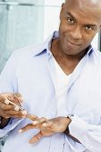 picture of fingernail  - African American man clipping fingernails - JPG
