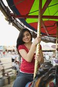 picture of carousel horse  - Mixed Race teenaged girl on carousel horse - JPG
