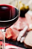 stock photo of charcuterie  - Glass of red wine with cold cuts assortment on the background - JPG
