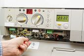 picture of furnace  - repair man is fixing a gas furnace - JPG