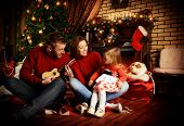picture of celebrate  - Happy family celebrating Christmas at home by the fireplace and the Christmas tree - JPG