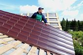 stock photo of roof tile  - Worker puts the metal tiles on the roof of a wooden house - JPG