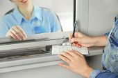 picture of cashiers  - Teller window with working cashier and female hands with claim check - JPG