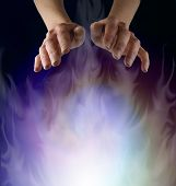 stock photo of ethereal  - Female hands hovering over a misty ethereal energy field on a black background - JPG