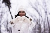 image of knitwear  - Woman making heart shape wearing knitwear gloves  - JPG