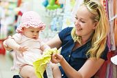 foto of apparel  - woman choosing children apparel with little baby child girl on hands in clothing shop supermarket - JPG