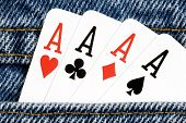 image of ace spades  - Horizontal close up shot of four aces in a denim pocket - JPG