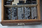 picture of armoire  - Old vintage metal printing press symbols in a drawer - JPG