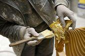 picture of carpenter  - Carpenter Applying Golden Leaf To A Furniture Inside The Carpenter - JPG