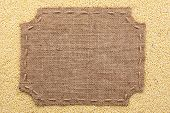 stock photo of stitches  - Figured frame with burlap and stitches with place for your text lying on millet grains as a background - JPG