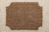 picture of stitches  - Figured frame with burlap and stitches with place for your text lying on rice grains as a background - JPG