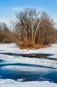 picture of water-mill  - Chunks of ice swirl in the currents of the Big Blue River as water cascades over an old grist mill dam in Edinburgh Indiana - JPG
