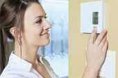 picture of carbon-footprint  - A woman set the thermostat at house - JPG