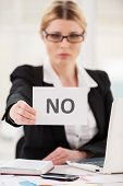 image of only mature adults  - Serious mature woman in formalwear saying no to you while stretching out a paper - JPG
