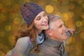 stock photo of extreme close-up  - Carefree couple in warm clothing against close up of christmas lights - JPG