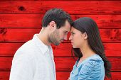 stock photo of outrageous  - Angry couple staring at each other against red wooden planks - JPG