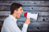 picture of outrageous  - Young man shouting through megaphone against grey wooden planks - JPG