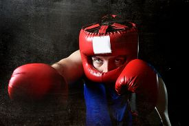 picture of headgear  - amateur boxer man training shadow boxing with red fighting gloves and headgear protection throwing angry right punch attack isolated on grunge dirty background - JPG