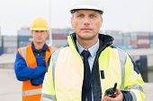 picture of coworkers  - Portrait of confident worker standing with coworker in background at shipping yard - JPG