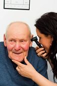 picture of otoscope  - Smiling patient enjoying hearing examination with otoscope - JPG