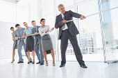 image of rope pulling  - Business team pulling the rope in the office - JPG