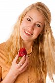 picture of strawberry blonde  - Beautiful blond cheerful caucasian woman eats a big red strawberrie isolated over white - JPG