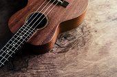 foto of ukulele  - Close up of ukulele on old wood background with soft light Vintage tone - JPG