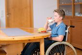 stock photo of bap  - disabled boy in wheelchair is drinking milk and eating in the living room - JPG