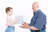 image of granddaughters  - Portrait of a small pretty granddaughter standing in front of her smiling grandfather and giving him a present in a beautiful box while he is looking very happy - JPG