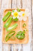 stock photo of aloe-vera  - Close up Aloe vera in wooden plate on wooden background - JPG