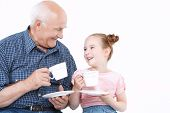 stock photo of granddaughters  - Portrait of a grandfather wearing blue checkered and his small pretty granddaughter playing drinking tea from white cups smiling happily - JPG