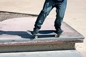 pic of skate  - Close up of a skateboarders feet while skating across a rail at the skate park - JPG