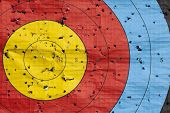 image of archery  - Archery target close up with many arrow holes in gold red blue and black - JPG