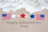 stock photo of usa flag  - Happy Independence Day USA background with flag on the sandy beach  - JPG