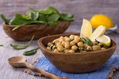 foto of chickpea  - Spiced chickpeas with spinach in a wooden bowl and on wooden table - JPG