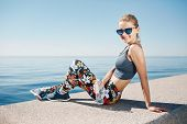image of bottle water  - Young fitness blonde woman hold bottle water after fit at beach and looking at camera - JPG