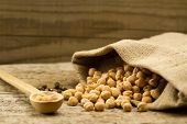 foto of chickpea  - scattered chickpeas from a jute bag with a spoon on old wooden background  - JPG