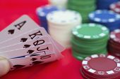 stock photo of ace spades  - poker player holding 10 to Ace spade straight flush of pokers beside lots of chips - JPG