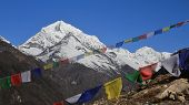 foto of snow capped mountains  - Colorful prayer flags and snow capped mountains scene near Namche Bazar - JPG
