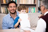 stock photo of psychologist  - Little boy and his smiling father talking with psychologist - JPG