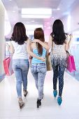 image of shopping center  - Rear view of teenage girls walking in the shopping center together while carrying shopping bags - JPG