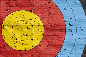 stock photo of archery  - Archery target close up with many arrow holes in gold red blue and black - JPG