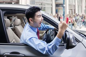 stock photo of annoying  - Portrait of annoyed male entrepreneur screaming and showing middle finger while driving a car - JPG