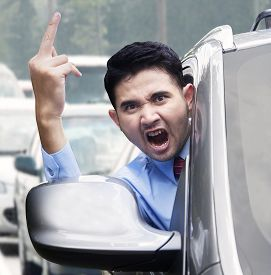 image of middle finger  - Portrait of furious businessman showing a middle finger while driving a car on the road  - JPG