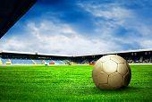 Постер, плакат: Футбольный мяч на поле стадиона с синим небом