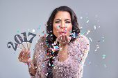 Pretty glamourous woman welcoming the new year 2017 blowing confetti into camera, photobooth style i poster